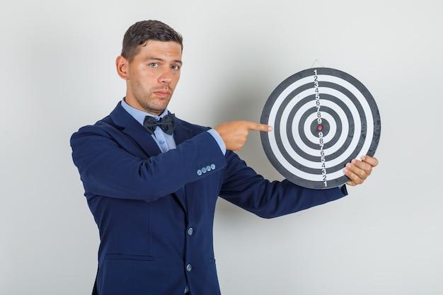 Jonge man wijzende vinger op dartbord in pak en op zoek naar serieus.