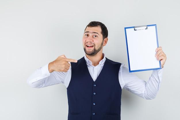 Jonge man wijzende vinger op klembord in overhemd, vest en op zoek zelfverzekerd
