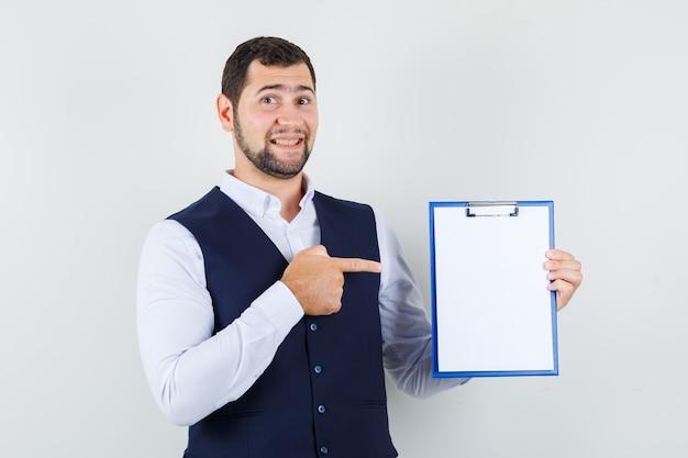 Jonge man wijzende vinger op klembord in shirt, vest en vrolijk op zoek