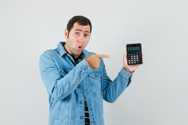 Jonge man wijzende vinger op rekenmachine in t-shirt, jasje en op zoek verrast. vooraanzicht.