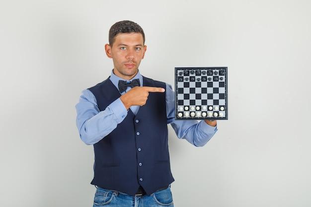Jonge man wijzende vinger op schaakbord in pak, jeans