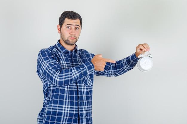 Jonge man wijzende vinger op wekker in geruit overhemd en bezorgd op zoek.