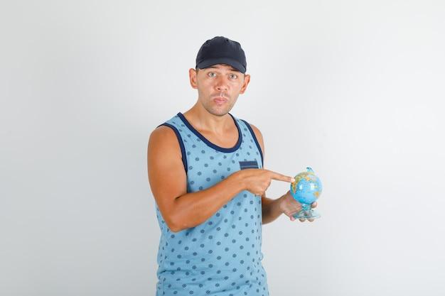 Jonge man wijzende vinger op wereldbol in blauw hemd met pet en op zoek verward