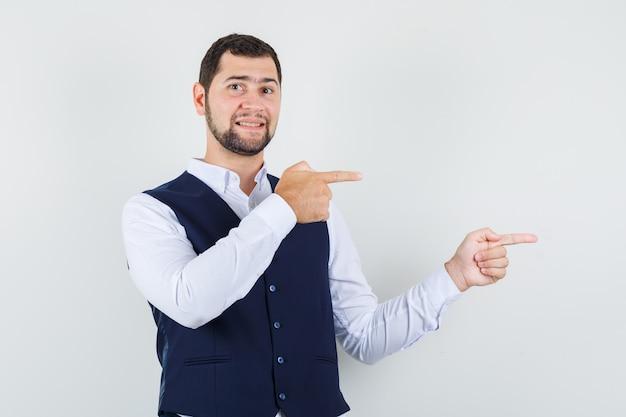 Jonge man wijzende vingers naar kant in overhemd, vest en op zoek positief