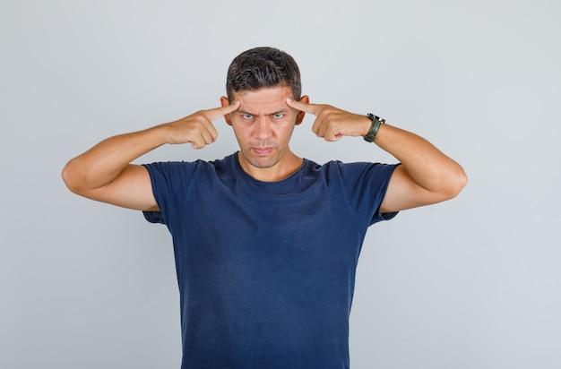 Jonge man wijzende vingers naar zijn hoofd in donkerblauw t-shirt en op zoek naar strikte, vooraanzicht.