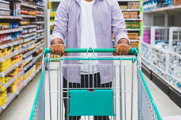 Jonge man winkelen bij de supermarkt.