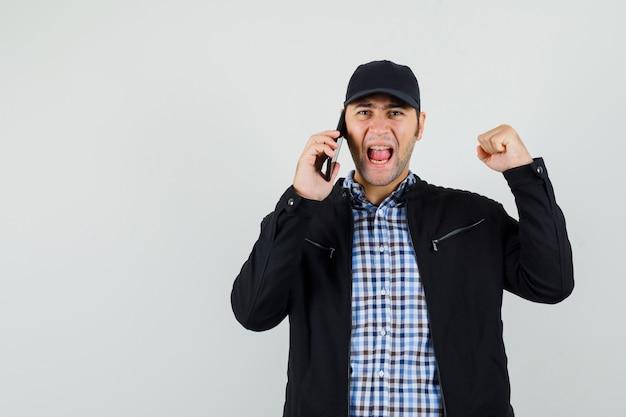 Jonge man winnaar gebaar tonen, praten op mobiele telefoon in shirt, jas, pet en op zoek gelukkig. vooraanzicht.