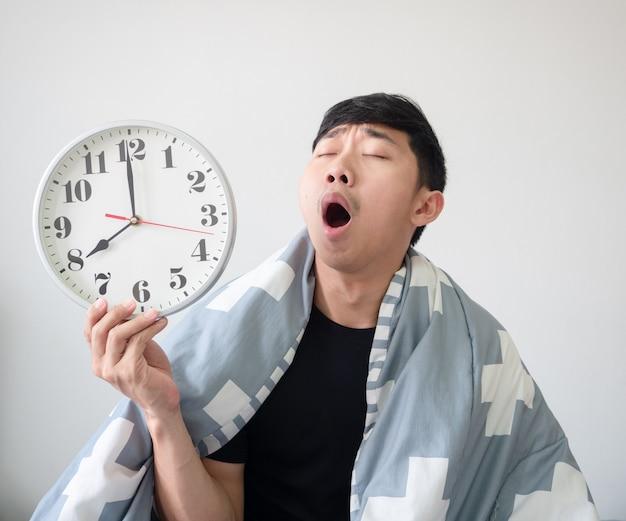 Jonge man wordt wakker met een deken die zijn lichaam bedekt en voelt zich slaperig gapen in zijn gezicht terwijl hij de klok in de hand houdt
