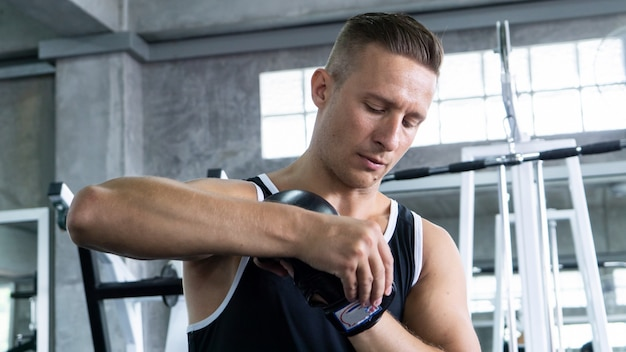 Jonge man workout in fitness gym op onscherpe achtergrond. atletische man hard trainen. sport co