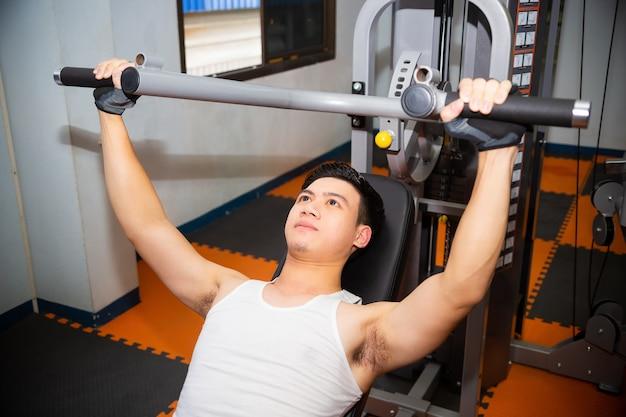 Jonge man workouts op fitness gym