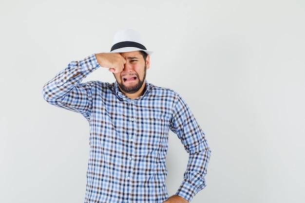 Jonge man wrijft oog terwijl hij huilen als een kind in geruit overhemd, hoed en beledigd kijkt