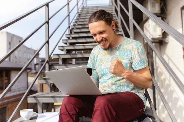 Jonge man, zakenman op zoek naar werk met laptop buitenshuis,