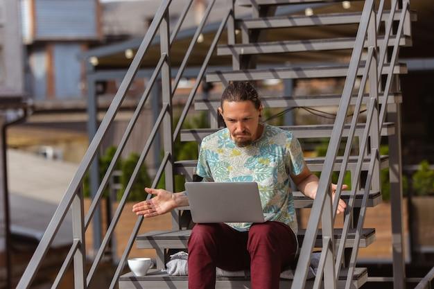 Jonge man zakenman op zoek naar werk met laptop buitenshuis
