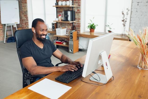 Jonge man, zakenman thuis, kijkend op een leeg zwart computerscherm, monitor.