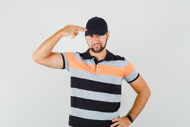 Jonge man zelfmoordgebaar maken in t-shirt, pet en op zoek zelfverzekerd. vooraanzicht.