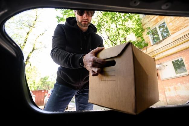 Jonge man zet een doos in de kofferbak van een auto