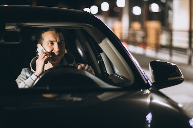 Jonge man zijn auto rijden 's nachts en praten over de telefoon