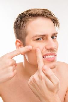 Jonge man zijn gezicht aan te raken en puistje te verpletteren