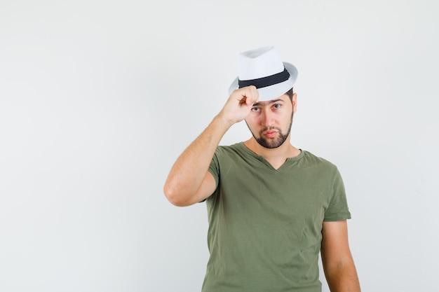 Jonge man zijn hoed in groen t-shirt aan te raken en serieus te kijken