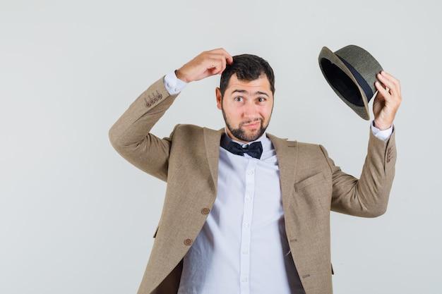 Jonge man zijn hoed opstijgen en hoofd krabben in pak, hoed en aarzelend, vooraanzicht op zoek.