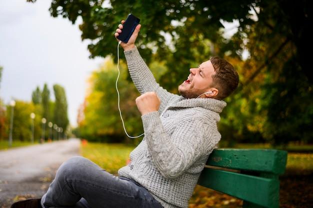 Jonge man zingen op een bankje in het park