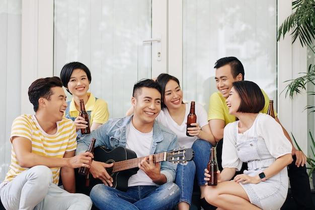 Jonge man zingen voor vrienden
