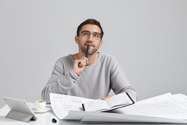 Jonge man zit aan bureau en doet papierwerk