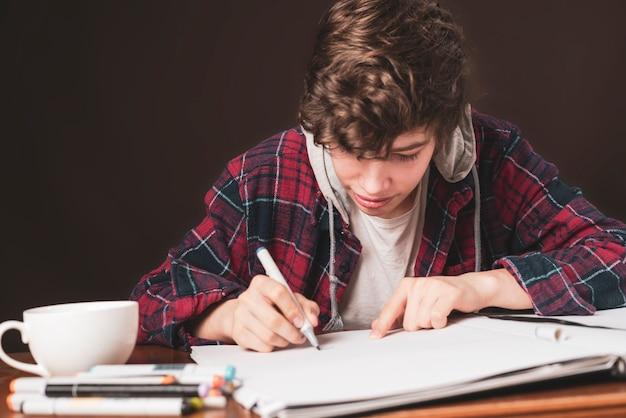 Jonge man zit aan tafel en maakt foto's in zijn notitieboekje met marker b
