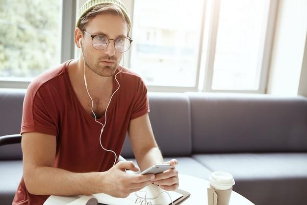 Jonge man zit in café luisteren naar muziek