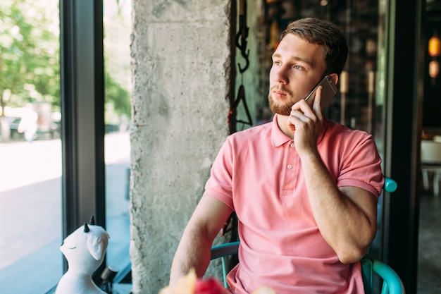 Jonge man zit in café met laptop en telefoon, werken, online winkelen, hipster