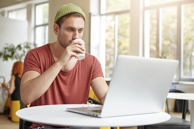 Jonge man zit in café met laptop