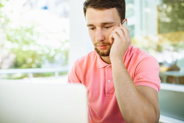 Jonge man zit in café op straat, buitenshuis met laptop en praten over de telefoon