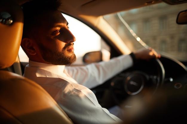 Jonge man zit in de auto en denkt aan iets tijdens het rijden