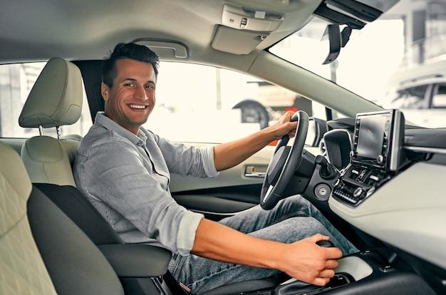 Jonge man zit in de auto en kiest een nieuw voertuig in de autodealer.