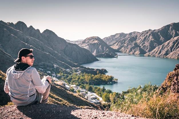 Jonge man zit in de vallei naast een reservoir in mendoza argentinië