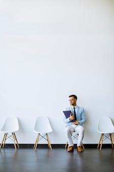 Jonge man zit in de wachtkamer met een map in de hand voor een interview