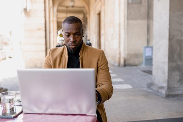 Jonge man zit in een coffeeshop en met behulp van laptop.