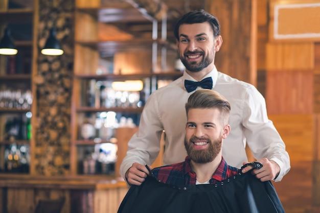 Jonge man zit in een kapperszaak vrolijke voorbereiding op het kapsel