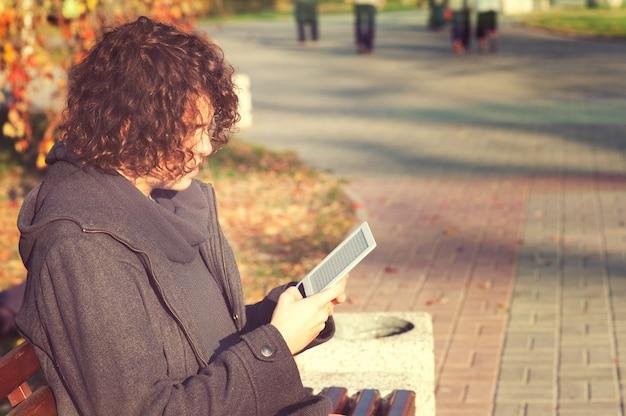 Jonge man zit in herfst park en lees het elektronische boek.