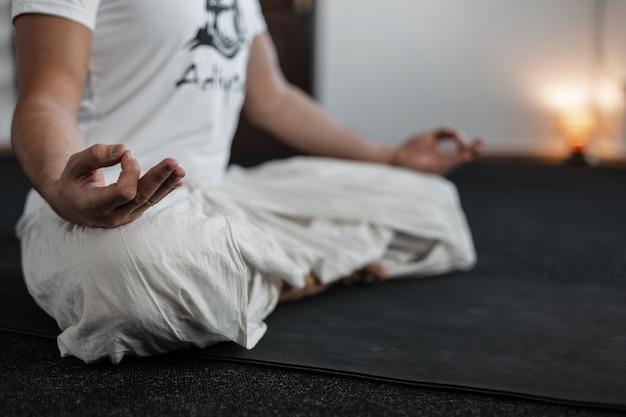Jonge man zit in lotushouding en mediteert. trainer man doet yoga. detailopname.