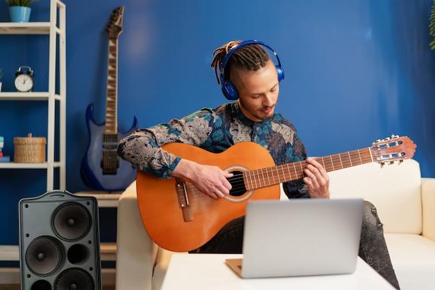 Jonge man zit in zijn kamer en gitaar les kijken op laptop