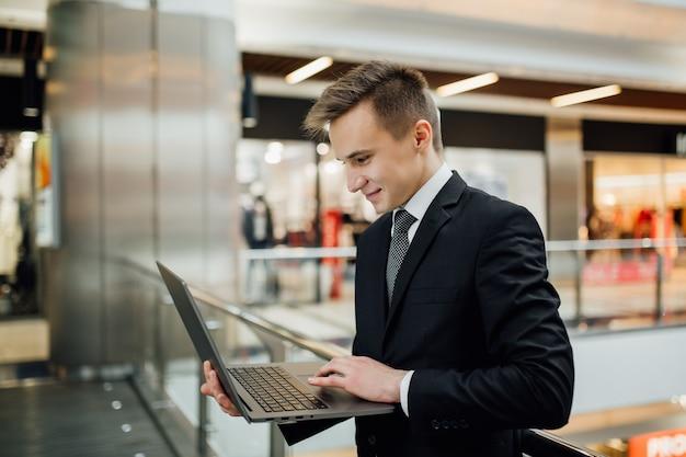 Jonge man zit laptop online chatten met vrienden. portret van kaukasische zakenman die in wandelgalerij, binnen, positieve gezichtsemoties werkt