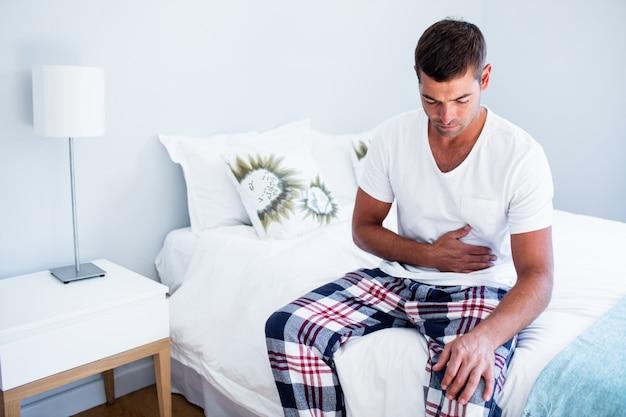 Jonge man zit met buikpijn op bed