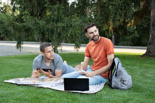 Jonge man zit met een laptop op gras op een universiteitscampus en maakt aantekeningen in notitieblok. man iets uit te leggen aan haar vriend in laptop.