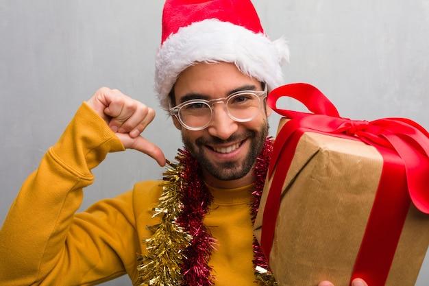 Jonge man zit met geschenken vieren kerstmis wijzende vingers, voorbeeld te volgen