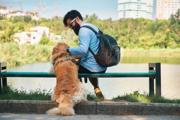 Jonge man zit met zijn hond op de stoel in het park