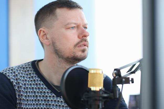 Jonge man zit microfoon in opnamestudio Premium Foto