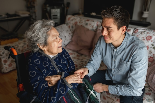 Jonge man zit naast een oude zieke oude vrouw in een rolstoel die haar handen neemt tijdens het praten en glimlachen. familie, thuiszorgconcept.