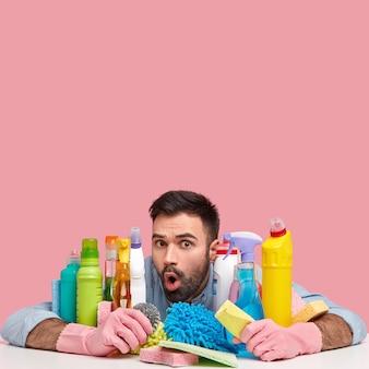 Jonge man zit naast schoonmaakmiddelen