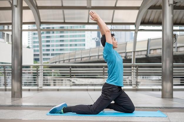 Jonge man zit oefening met pose yoga meditatie op blauwe mat in de stad in